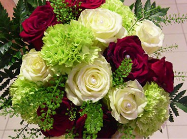Bouquet rond de roses blanches gros boutons dans un écrin de feuillage.